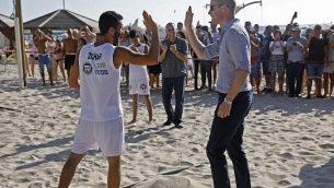 الأمير ويليام (من اليمين) يصافح لاعب كرة طائرة شاطئية خلال زيارة قام بها برفقة رئيس بلدية تل أبيب في المدينة الساحلية، 26 يونيو، 2018. (AFP PHOTO / POOL / MENAHEM KAHANA)
