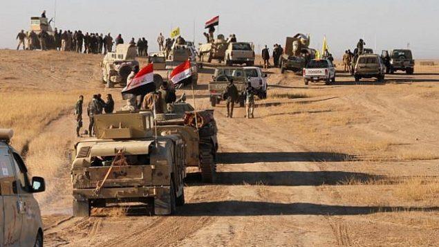 القوات العراقية، المدعومة من عناصر 'الحشد الشعبي'، تتقدم في الصحراء الغربية في منطقة الحضر شمال العراق، على بعد 105 كيلومترات جنوبي الموصل، 23 نوفمبر، 2017،  أثناء محاولتها تطهير ما تبقى من مقاتلي تنظيم 'الدولة الإسلامية'. (AFP/Stringer)