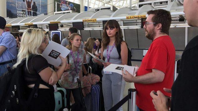 تحدث عضو 'إف نات ناو' إندي راتو مع المشاركين في رحلة بيرثرايت عند تسجيل وصولهم في مطار JFK في نيويورك، يوم الاثنين، 18 حزيران، 2018. (Steven Davidson/ Times of Israel)