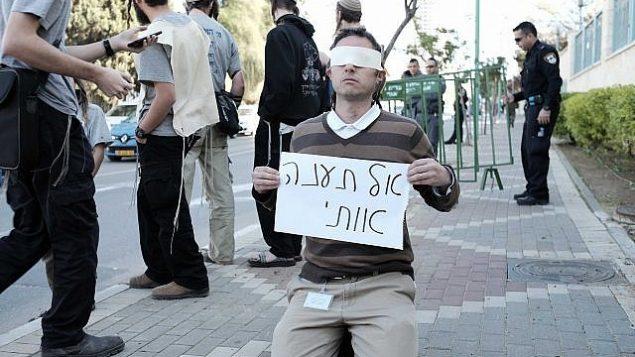 """ناشط من اليمين يحمل لافتة كُتب عليها """"لا تعذبني"""" خارج مبنى المحكمة في مدينة بيتح تيكفا حيت تجرى محاكمة المشتبه بهما في هجوم دوما، 28 ديسمبر، 2015. Neuberg/Flash90)"""
