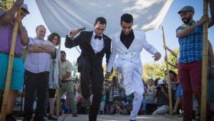 زوجان مثليان في حفل زفاف رمزي تحت مظلة زفاف تقليدية خلال موكب الفخر السنوي في القدس، 21 يوليو 2016. (Hadas Parush / Flash90)