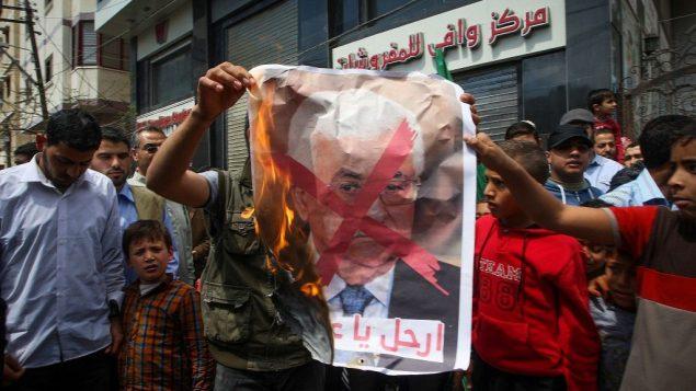 متظاهرون في غزة يحملون صورة مشطوبة لرئيس السلطة الفلسطينية محمود عباس الله في خان يونس، 14 ابريل 2017 (Abed Rahim Khatib/Flash90)