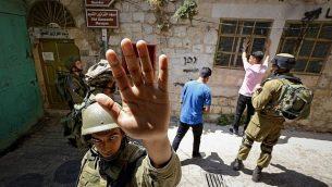 جندي إسرائيلي يحاول منع مصور من التصوير خلال قيام جنود بتفتيش رجال فلسطينيين في مدينة الخليل في الضفة الغربية، 22 يونيو، 2017. (Wisam Hashlamoun/Flash90)