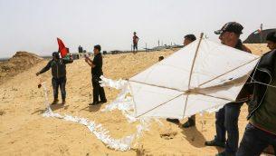 طائرة ورقية محملة بزجاجة حارقة يتم التجهيز لإطلاقها خلال اشتباكات بين فلسطينييين وقوات الامن الإسرائيلية عند حدود غزة، شرقي خان يونس، 20 أبريل 2018 (Abed Rahim Khatib/Flash90)