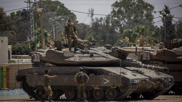جنود إسرائيليون بالقرب من دبابة داخل قاعدة عسكرية بالقرب من الحدود بين إسرائيل وغزة، 30 مايو 2018 (Yonatan Sindel/Flash90)