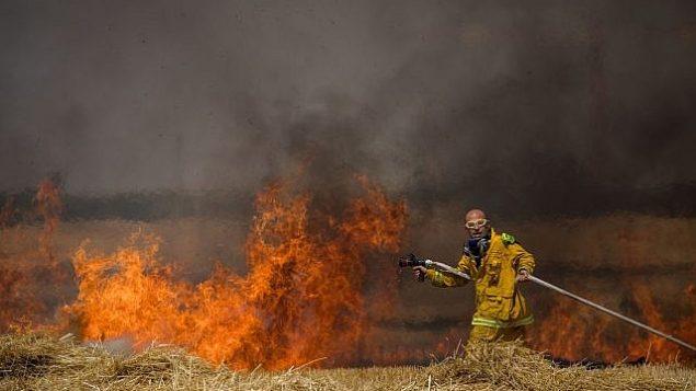 رجال إطفاء إسرائيليون يعملون على إخماد النيران في حقل قمح ناجم عن تطيير طائرات ورقية من قبل متظاهرين فلسطينيين، بالقرب من الحدود مع قطاع غزة، 30 مايو، 2018.(Yonatan Sindel/Flash90)