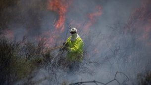 رجال الإطفاء يعملون على إخماد النار في حقل بعد اندلاع حريق فيه ناجم عن طائرات ورقية أطلقها فلسطينيون في قطاع غزة، بالقرب من الحدود مع قطاع غزة، 5 يونيو، 2018. (Yonatan Sindel/Flash90)