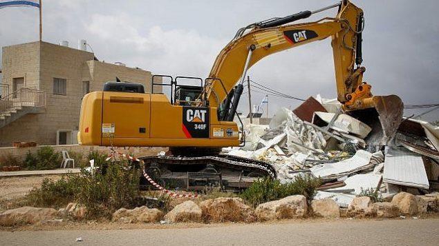 جرافة تهدم منازل في بؤرة نتيف هأفوت الاستيطانية في 13 يونيو، 2018. (Gershon Elinson/Flash90)