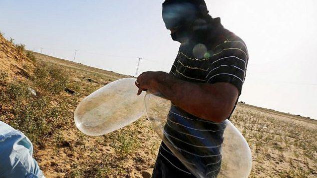 ملثم فلسطيني يعد بالونا سيقوم تحميله بمواد حارقة لإطلاقه باتجاه إسرائيل بالقرب من الحدود الإسرائيلية مع غزة، في مدينة رفح بجنوب قطاع غزة، 17 يونيو، 2018.  (Abed Rahim Khatib/Flash90)