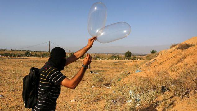 ملثم فلسطيني يطلق بالونا محملا بمواد حارقة باتجاه إسرائيل من مدينة رفح في جنوب قطاع غزة في 17 يونيو، 2018 (Abed Rahim Khatib/Flash90)