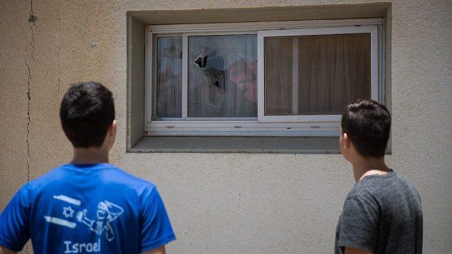 إسرائيليان في كيبوتس بالقرب من غزة يتفحصان مكان سقوط صاروخ تم إطلاقه من غزة بالقرب من منازل، ما تسبب بتحطيم نوافذ، 20 يونيو، 2018. (Yonatan Sindel/Flash90)