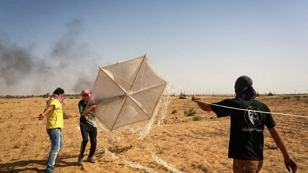 فلسطينيون يعدون طائرة ورقية محملة بمواد حارقة سيقومون بإطلاقها باتجاه جنود إسرائيل من رفح، في جنوب قطاع غزة، 22 يونيو، 2018.  (Abed Rahim Khatib/Flash90)