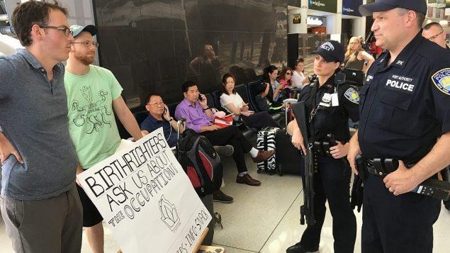 أبلغت سلطة المطار أعضاء 'إف نات ناو'  أنه يجب عليهم الكف عن التحدث إلى مشاركين في رحلة بيرثرايت إذا لم يكن لديهم تصريح، في مطار JFK في نيويورك، يوم الاثنين 18 يونيو، 2018. (Steven Davidson / Times of Israel)