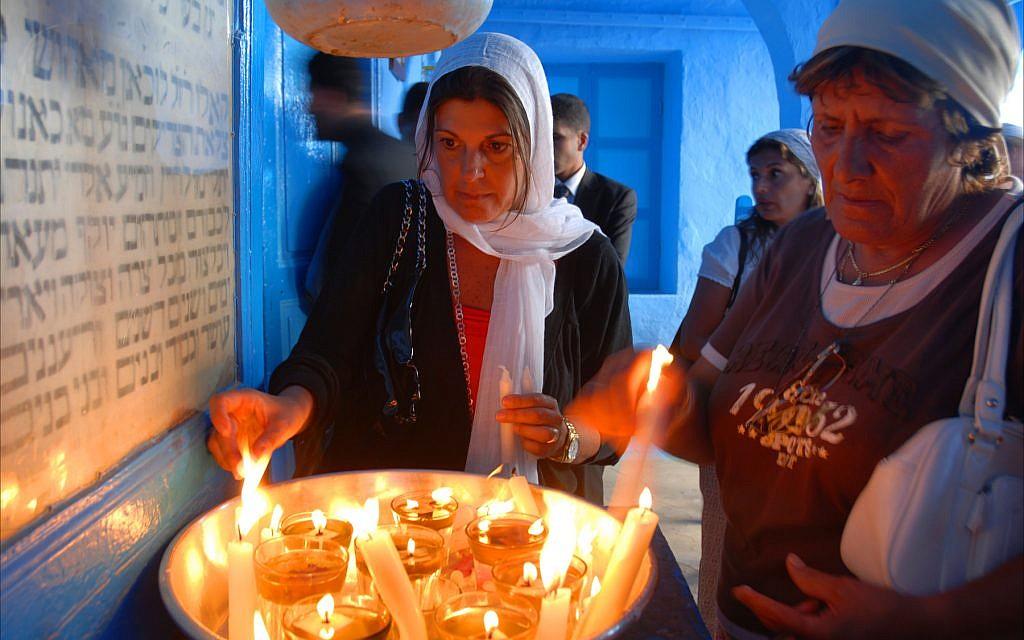 نساء يهوديات يضيئن الشموع في معبد غريبا في جربة بتونس. (Larry Luxner/ Times of Israel)