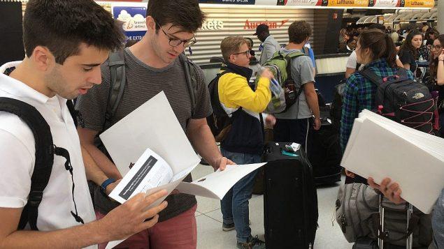 المشاركون في رحلة بيرثرايت يقرأون المواد التي تم توزيعها عليهم في مطار جون كنيدي في نيويورك يوم الإثنين 18 يونيو 2018. (Steven Davidson / Times of Israe)