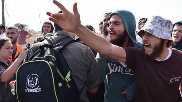 شبان من اليمين المتطرف يحتجون على أمر محكمة بهدم 17 مبنى في بؤرة تبواح الغربية الاستيطانية غير القانونية. (الشرطة الإسرائيلية)