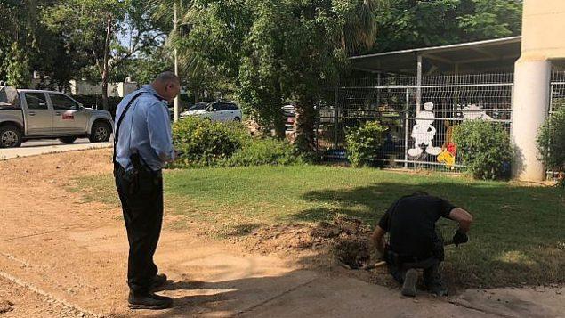 خبير متفجرات من الشرطة يتعامل مع صاروخ اطلق من غزة وسقط امام حضانة في احدى بلدات منطقة اشكول، 20 يونيو 2018 (Eshkol region)