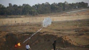 """فلسطينيان يساعدان في إطلاق """"طائرة ورقية"""" من قطاع غزة إلى الأراضي الإسرائيلية خلال مظاهرات حاشدة على طول السياج الحدودي في 8 يونيو / حزيران 2018. (الجيش الإسرائيلي)"""