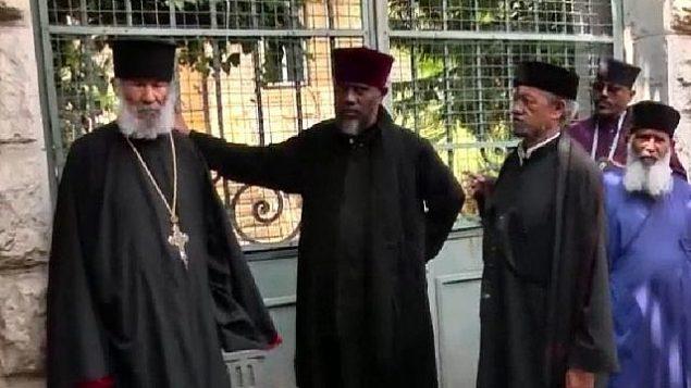 تجمع رهبان إثيوبيون خارج مجمع الكنيسة المملوك للكنيسة الإثيوبية والتي طردتهم منها الشرطة في 31 مايو 2018. يقف الأكبر البالغ من العمر 84 عامًا إلى اليسار. (Channel 10 News screenshot)