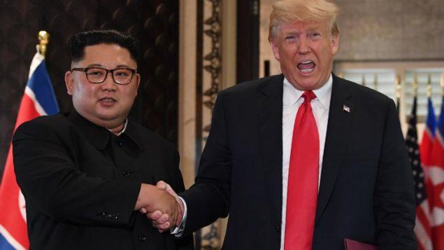 مصافحة بين الرئيس الأمريكي دونالد ترامب من اليمين) وزعيم كوريا الشمالية كيم جونغ أون خلال لقائهما في مستهل القمة الأمريكية -الكورية الشمالية التاريخية  التي جمعتهما في فندق 'كابيلا' في جزيرة سنتوسا في سنغافورة، 12 يونيو، 2018 (AFP PHOTO / SAUL LOEB)
