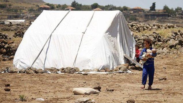 فتاة سورية نازحة من محافظة درعا فرت من القصف من قبل القوات الموالية للحكومة تحمل طفلاً في مخيم مؤقت في محافظة القنيطرة، جنوب غرب سوريا، بالقرب من الحدود مع مرتفعات الجولان، في 22 يونيو / حزيران 2018. (AFP/Mohamad Abazeed)