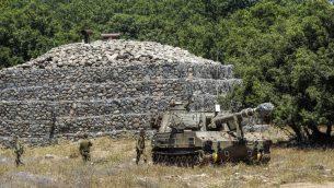 جنود اسرائيليون امام مبنى محصن مع مدفع نقال امامخ بالقرب من الحدود السورية في مرتفعات الجولان، 1 يوليو 2018 (AFP Photo/Jalaa Marey)