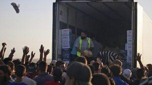 سوريون نازحون فروا من قصف قوات النظام السوري في درعا، يتجمعوت للحصول على مساعدات غذائية في مخيم بالقرب من الحدود الاردنية وبلدة نصيب، جنوب سوريا، 2 يوليو 2018 (AFP PHOTO / Mohamad ABAZEED)