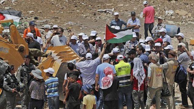 يرفع المتظاهرون الأعلام الفلسطينية وهم يحاولون منع جرافات من فتح طريق وصول إلى قرية الخان الأحمر البدوية في الضفة الغربية في 4 يوليو 2018. (AFP Photo/Ahmad Gharabli)