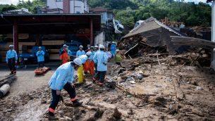 طواقم اغاثة يخلون الحطام من شارع في منطقة اصيبت بفياضانات في هيروشيما، 9 يوليو 2018 (MARTIN BUREAU / AFP)