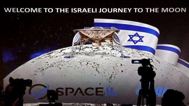 صحفيون يجهزون لحضور مؤتمر صحفي يعقده قسم الفضاء في شركة الصناعات الجوية الإسرائيلية للاعلان عن اطلاق مركبة فضائية الى القمر، 10 يوليو 2018 (AFP PHOTO / THOMAS COEX)