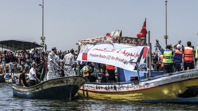 ناشطون يرافقون قارب على متنه فلسطينيين اصيبوا خلال الاشتباكات عند السياج الامني حول غزة، اثناء محاولته كسر الحصار البحري الذي تفرضه اسرائيل، 10 يوليو 2018 (Mahmud Hams/AFP)