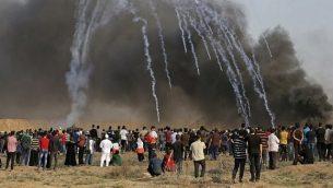 صورة تم التقاطها في 13 يوليو 2018 تظهر عبوات الغاز المسيل للدموع التي أطلقتها القوات الإسرائيلية وهبطت وسط المتظاهرين خلال مظاهرة على طول الحدود مع إسرائيل شرق مدينة غزة. (AFP/Mahmud Hams)