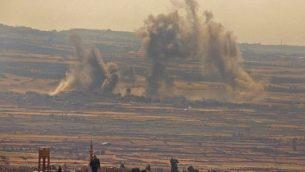 دخان يتصاعد جراء غارات جوية سورية وروسية مزعومة عبر الحدود في محافظة القنيطرة في جنوب شرق سوريا، كما تظهر من الجانب الإسرائيلي من هضبة الجولان، 16 يوليو، 2018.  (JALAA MAREY/AFP)