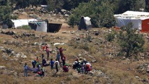 صورة تم  التقاطها في 17 يوليو، 2018 من هضبة الجولان تظهر لاجئين يقتربون من السياج الحدودي بين سوريا وإسرائيل من مخيم للنازحين السوريين بالقرب من بلدة بريقة السورية في محافظة القنيطرة الجنوبية. (AFP /JALAA MAREY)