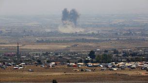 صورة التقطت من الطرف الإسرائيلي من مرتفعات الجولان تظهر الدخان يتصاعد فوق مباني خلال غارة جوية بالقرب من مخيم نازظحين سوريين في محافظة درعا جنوب سوريا، 18 يوليو 2018 (JALAA MAREY/AFP)