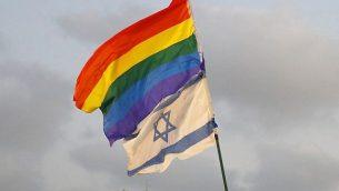 متظاهرون يرفعون العلم الإسرائيلي وعلم الفخر في مظاهرة في تل أبيب في 22 يوليو 2018، احتجاجا على قانون الحمل البديل الجديد الذي لا يشمل الأزواج المثليين. (AFP PHOTO / JACK GUEZ)