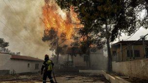 رجل إطفاء يحاول السيطرة على نقاط ساخنة خلال حرائق غابات في بلدة كينيتا، القريبة من أثينا، 23 يوليو، 2018. (VALERIE GACHE/AFP)