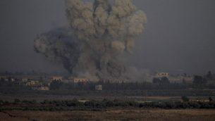 صورة التقطت من الطرف الإسرائيلي في مرتفعات الجولان تظهر الدخان يتصاعد من مباني في الطرف السوري من الحدود خلال غارات جوية سورية في محافظة القنيطرة، 25 يوليو 2018 (AFP / JALAA MAREY)