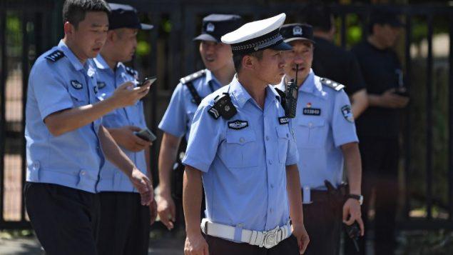عناصر شرطة صينيين امام السفارة الامريكية في بكين، في اعقاب انفجار بالقرب من السفارة، 26 يوليو 2018 (GREG BAKER / AFP)
