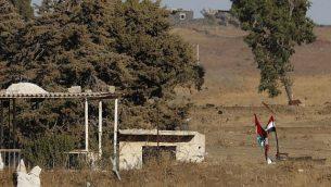 صورة تم التقاطها في 26 يوليو، 2018، بالقرب من كيبوتس عين زيفان في الجانب الإسرائيلي من هضبة الجولان، تظهر فيها الأعلام السورية (من اليمين) وأعلام حزب 'البعث' السوري (من اليسار) وهي ترفرف عبر الحدود إثر استعادة قوات النظام لسيطرتها على المنطقة من المتمردين.  (AFP Photo/Jack Guez)