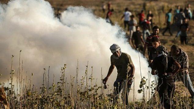 فلسطينيون يشاركون في مواجهات مع القوات الإسرائيلية على طول السياج الحدودي بين إسرائيل وقطاع غزة، شرق مدينة غزة في 27 يوليو / تموز 2018. (AFP Photo / Mahmud Hams)