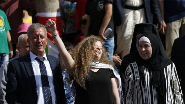 الناشطة الفلسطينية عهد التميمي (وسط الصورة) تقف بين والدها (وسط-يسار) ووالدتها (وسط-يمين) خلال مؤتمر صحفي في قرية النبي صالح الواقعة في الضفة الغربية في 29 يوليو، 2018، بعد إطلاق سراحها من السجن الإسرائيلي حيث قضت عقوبة بالسجن لمدة 8 أشهر. (/ AFP PHOTO / ABBAS MOMANI)