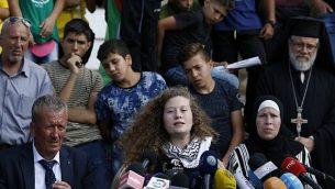 الناشطة الفلطسينية عهد التميمي (وسط الصورة) تجلس بين والدها باسم ووالدتها ناريمان خلال مؤتمر صحفي في قرية النبي صالح في الضفة الغربية، 29 يوليو، 2018. (AFP/ABBAS MOMANI)