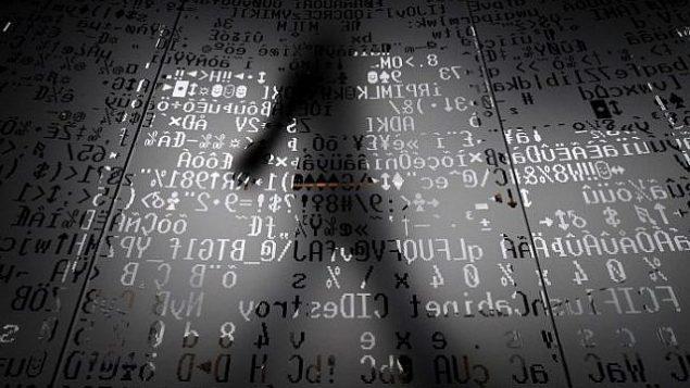 صورة تم التقاطها في 17 أكتوبر، 2016، تظهر موظفا يسير وراء جدار زجاجي مع رموز تشفير آلية في مقر عملاق الأمن الإلكتروني 'كاسبرسكي' في موسكو.  (AFP/Kirill KUDRYAVTSEV)