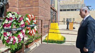 رئيس الوزراء بنيامين نتنياهو يضع إكليلاً من الزهور خلال الاحتفال الرسمي للدولة بمناسبة يوم ذكرى المحرقة الوطنية في متحف ياد فاشيم، في 27 أبريل 2014. (Haim Zach/GPO/Flash 90)
