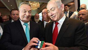رئيس الوزراء بينيامين نتنياهو ونظيره المجري فيكتور أوربان (من اليسار) يحملان مكعب روبيك في منتدى الأعمال المجري الإسرائيلي في العاصمة المجرية بودابست، 19 يوليو، 2017. (Haim Zach/GPO/Flash90)