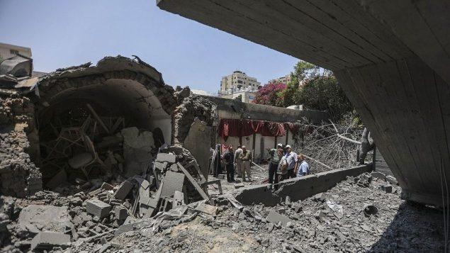 صبيان فلسطينيون يسيرون عبر حطام مبنى تضرر في غارات جوية إسرائيلية في مدينة غزة، 15 يوليو، 2018. (Wissam Nassar/Flash90)