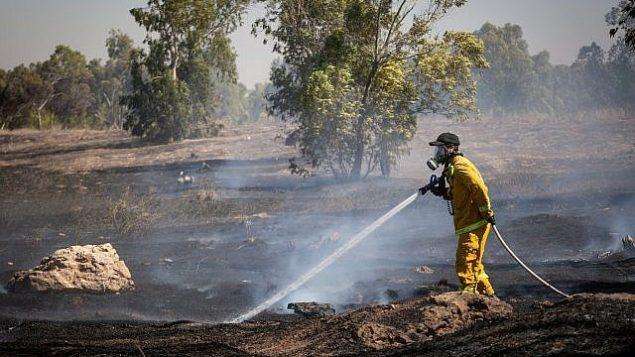 رجال إطفاء إسرائيليون يطفئون حريقا في حقل في جنوب إسرائيل ناجم عن طائرات ورقية أطلقها فلسطينيون في قطاع غزة، 27 يونيو، 2018 Flash90)
