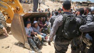 عناصر الشرطة الإسرائيلية خلال اشتباكات مع متظاهرين فلسطينيين في قرية خان الاحمر البدوية في الضفة الغربية، 4 يوليو 2018 (Flash90)