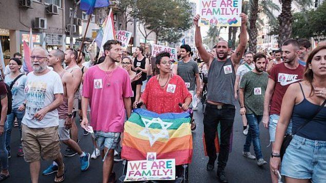 أفراد في المجتمع المثلي ومناصرين لهم يشاركون في مظاهرة ضد مشروع تعديل قانون في الكنيست يحرم الأزواج المثلية من أحقية استئجار الأرحام، 19 يوليو، 2018. (Tomer Neuberg/Flash90)